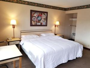 A bed or beds in a room at TravelStar Inn & Suites