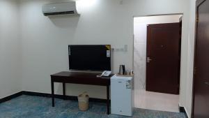 Uma TV ou centro de entretenimento em Dana Airport Furnished Apartments