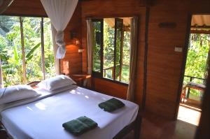 A bed or beds in a room at Khaosok Riverside Cottages - SHA Certified