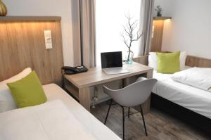 A television and/or entertainment center at Hotel Perlach Allee by Blattl