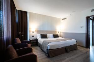 A bed or beds in a room at Catalonia Gran Hotel Verdi