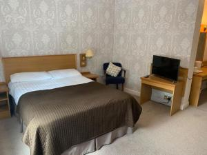 A bed or beds in a room at Waterford Lodge Hotel