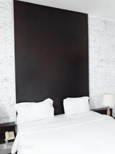 A bed or beds in a room at Ginasuite Kompleks27 Hotel