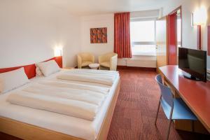 Ein Bett oder Betten in einem Zimmer der Unterkunft H2O-Hoteltherme