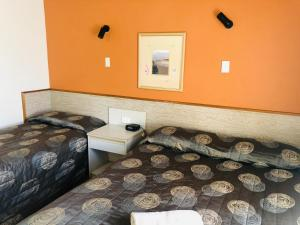 A bed or beds in a room at Panorama Motor Inn