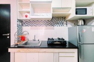 A kitchen or kitchenette at Homey 2BR Cervino Village Apartment By Travelio