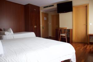 A bed or beds in a room at Hotel Miradoiro de Belvís