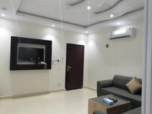 Uma TV ou centro de entretenimento em Fakhamat Al Orjoana & Suites