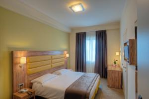 A bed or beds in a room at Giga Hotel
