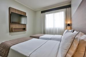 A bed or beds in a room at Wyndham Golden Foz Suítes