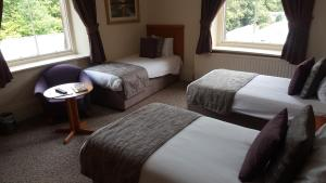 A bed or beds in a room at Keswick Country House Hotel