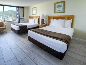 A bed or beds in a room at Waikiki Monarch Hotel