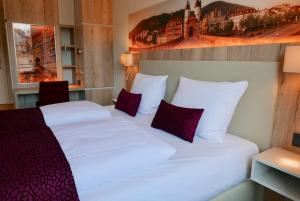 A bed or beds in a room at Rafaela Hotel Heidelberg