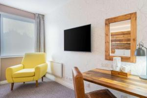 A television and/or entertainment center at Clarion Cedar Court Bradford Hotel