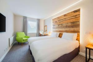 A bed or beds in a room at Clarion Cedar Court Bradford Hotel