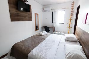 A bed or beds in a room at Hotel Gogó da Ema