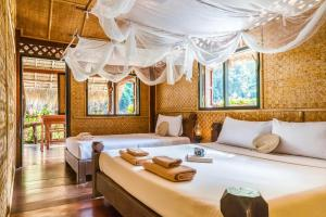 A bed or beds in a room at River Kwai Jungle Rafts - SHA Certified