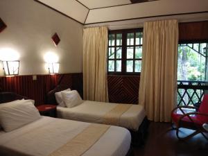 Ein Bett oder Betten in einem Zimmer der Unterkunft Sepilok Jungle Resort