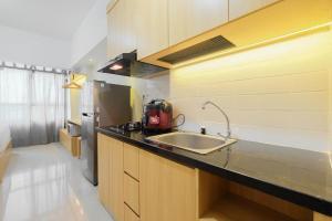 A kitchen or kitchenette at Modern Studio @ Springlake Summarecon Apartment By Travelio