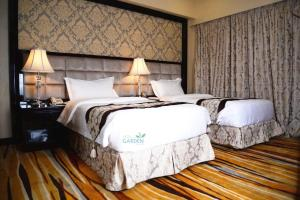 A bed or beds in a room at Garden Plaza Hotel