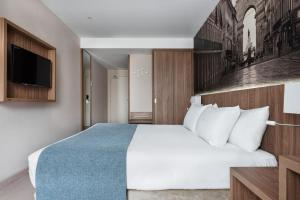 A bed or beds in a room at Exe Saldanha