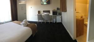 A bed or beds in a room at Nowra Motor Inn