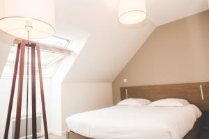 A bed or beds in a room at Terres de France - Appart'Hotel Quimper Bretagne