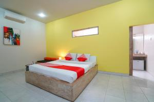 A bed or beds in a room at OYO 1638 Cityzen Renon Hotel