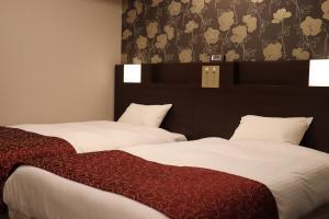 Ein Bett oder Betten in einem Zimmer der Unterkunft Hotel. Links Namba