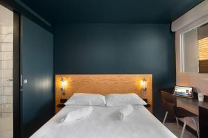A bed or beds in a room at Eklo Clermont Ferrand Centre Gare