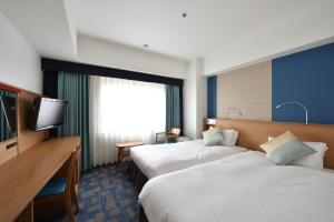A bed or beds in a room at Hotel Granvia Hiroshima