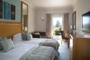 A bed or beds in a room at Buxted Park Country House