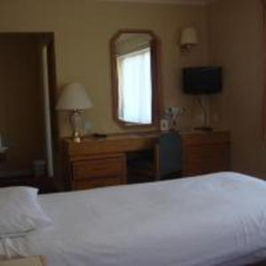 A bed or beds in a room at Carrington House Hotel