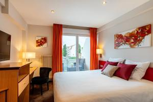 A bed or beds in a room at Europe Haguenau – Hotel & Spa