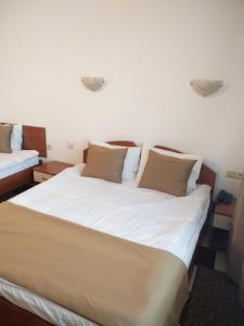 A bed or beds in a room at Slavyanska Beseda Hotel