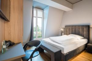 A bed or beds in a room at Hotel Cult Frankfurt City