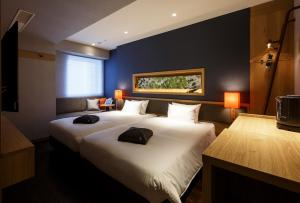 A bed or beds in a room at Hotel Forza Osaka Kitahama