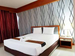 A bed or beds in a room at JP Emerald Hotel