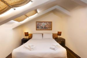 A bed or beds in a room at The Colony Hotel