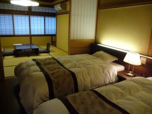 A bed or beds in a room at Jizokan Matsuya Ryokan