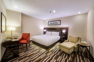 A bed or beds in a room at Avari Xpress Gulberg