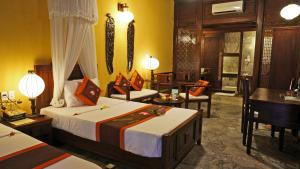 A bed or beds in a room at Vinh Hung Heritage Hotel