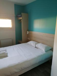 A bed or beds in a room at Kyriad Direct Nantes la Beaujoire