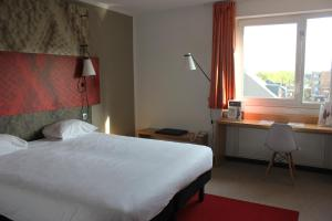 A bed or beds in a room at ibis Mons Centre Gare
