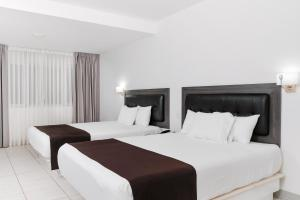 A bed or beds in a room at Costa del Sol Wyndham Tumbes