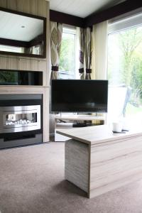 A television and/or entertainment centre at Herons Lake Retreat Lodges