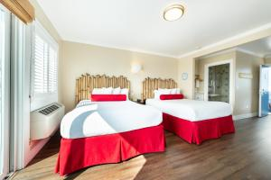 A bed or beds in a room at Beach Street Inn and Suites