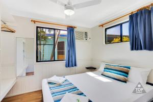 A bed or beds in a room at Coral Coast Tourist Park