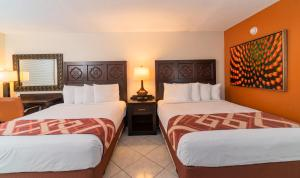 A bed or beds in a room at Sevilla Inn Kissimmee- Near Disney