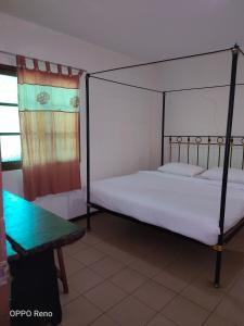 A bed or beds in a room at Kuching Waterfront Lodge